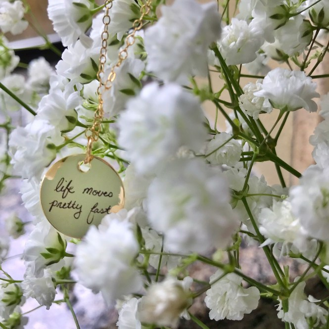 "Gold Disc necklace that says ""life moves pretty fast"" dangling on gold chain from a bouquet of baby's breath flowers"