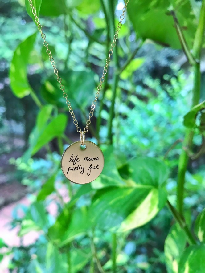 "Custom Handwritten Gold Disc Necklace with ""life moves pretty fast"" written in cursive"