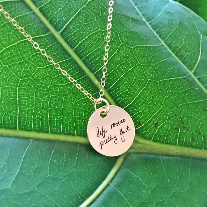 "Custom Handwritten Gold Disc Necklace with ""life moves pretty fast"" written in cursive in front of fiddle leaf fig"
