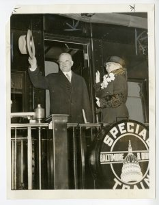 President and Mrs. Hoover photographed in the rear of a train that they traveled in.