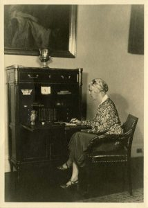"""Lou Henry Hoover sitting at the """"Monroe Desk"""" ithat was reproduced for the White House collection. ca 1931"""