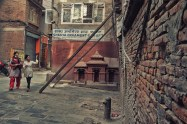 Two women walk with uncertainity near the almost falling house in Ason, Kathmandu.