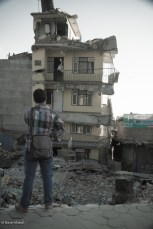Local man watches with astonishment towards the broken house in Balkhu, Kathmandu