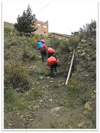 HOPE Bolivia Volunteers climbing up the hill with red bags full of gifts