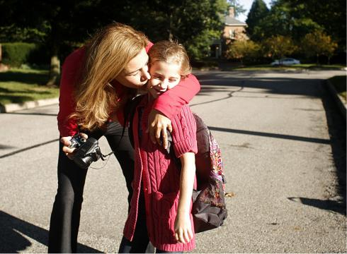 Mother Kissing Daughter Before Going Back to School