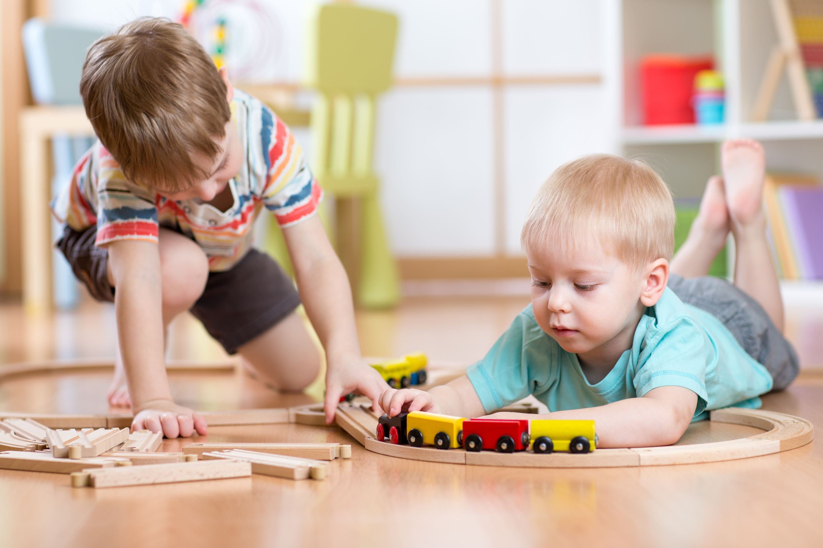 cute children playing with wooden train. toddler kids play with