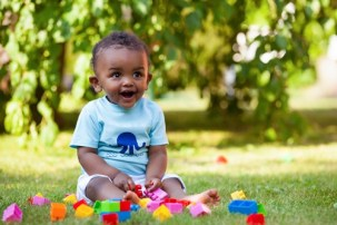 Baby boy playing with blocks in a park