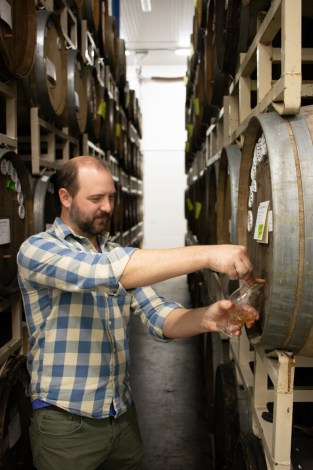 Kevin Martin pours a sample from a barrel in the Cascade blending facility.