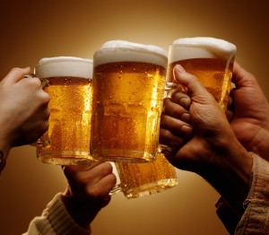 FOUR HANDS MALE AND FEMALE TOAST WITH MUGS OF BEER