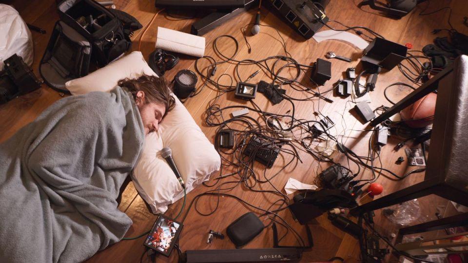 Bo Burnham se acurruca con una manta en el suelo, rodeado por un desorden de equipos de producción en Inside de Bo Burnham