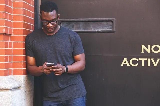 hombre afroamericano viendo el móvil