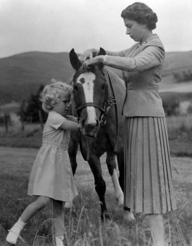 Princess Anne helps her mother Queen Elizabeth adjust the bridle of the pony 'Greensleeves' in the grounds of Balmoral on their summer holidays
