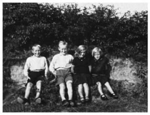 Gunner Møller Rasmussen med sine tre søskende på bænken i diget mod Serridslevgård, 1932