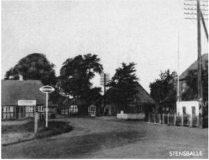 """Stensballe omkring 1920. Bygaden er set fra øst ved udkørslen fra Stensballegård. Til venstre ses en lille del af """"smedjedammen"""", der sidst i 1920érne blev fyldt op, samtidig blev den gamle skole, der lå ved indkørslen til Stensballegård nedrevet."""