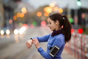 graphicstock-beautiful-young-woman-in-the-city-with-smart-phone-smartwatch-and-earphones-listening-music-using-a-fitness-app-for