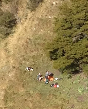 A paramedic and other personnel prepare the injured man for winching aboard the Westpac Rescue Helicopter.
