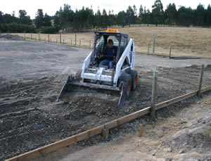 AP65 - a mix of sand and gravel - is spread before compaction. This is a key element in creating an all-weather arena, keeping the undesirable subsoil material from coming up and playing havoc with the top layers.