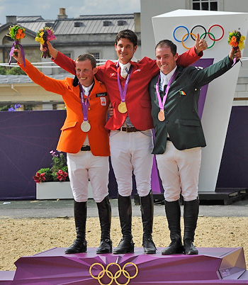 On the medal podium for the jumping individual final at the London 2012 Olympic Games equestrian venue at Greenwich Park today: (L to R) Gerco Schroder (NED) silver, gold medallist Steve Guerdat (SUI) and bronze medallist Cian O'Connor (IRL).  Photo: FEI/Kit Houghton.