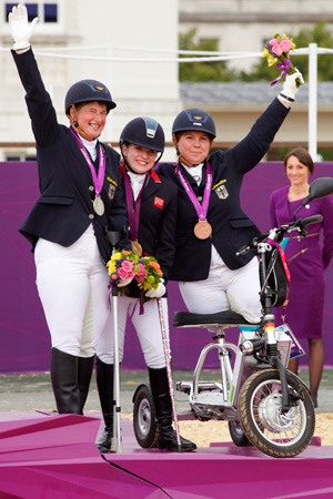 Natasha Baker from Great Britain scoops the first equestrian gold medal in Grade II. Britta Napel on the left and Angelika Trabert (GER) on the right taking silver and bronze