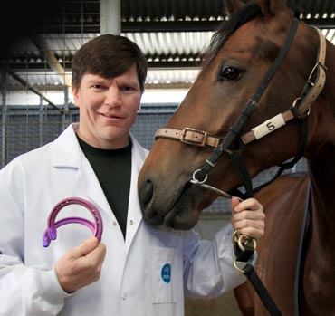 CSIRO researcher Chad Henry, presents the new race shoes to Melbourne-based racehorse Titanium Prints.