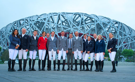 """International riders together with Michael Mronz and Frank Kemperman in front of the """"Bird's Nest"""" Olympic Stadium, from left, Meimei Zhu (CHN), Roger-Yves Bost (FRA), Scott Brash (GB), Penelopes Leprevost (FRA), Frank Kemperman (NL), Kevin Staut (FRA), Ludger Beerbaum, Michael Mronz, Marco Kutscher (all from Germany), Ben Maher (GB), Laura Kraut (USA), Nick Skelton (GB) and Jane Richard Philips (SUI)."""
