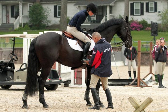 George Morris adjusts Sloane Cole's foot in the stirrup before the start of the gymnastics.