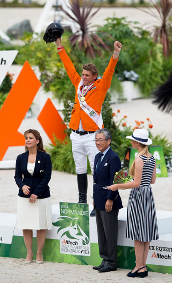 The Netherlands' Jeroen Dubbeldam celebrates victory in the individual Jumping final after receiving the gold medal from IOC Member, Tsunekazu Takeda, Vice-President of the Tokyo 2020 Organising Committee and Member of the FEI Olympic Council, and FEI President Princess Haya.