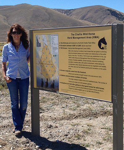 Andrea Maki with a new BLM sign on the Challis HMA. The sign acknowledges Wild Love Preserve for its volunteer work.
