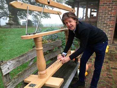 Paul McCartney signs the Moonstar rocking horse.