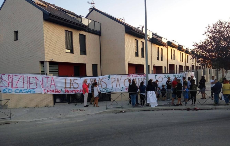 Pancarta reivindicativa frente a uno de los lineales de casas afectados.