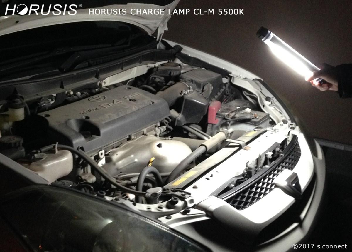 自動車用整備ライトでエンジンルームを点検している写真