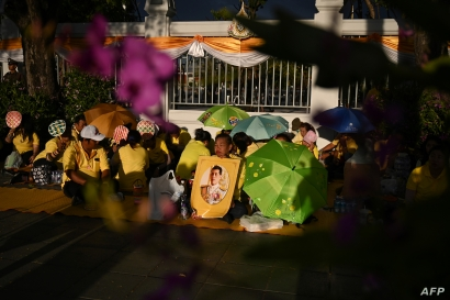People gather holding a portrait of Thailand's King Maha Vajiralongkorn along a sidewalk near the Grand Palace in Bangkok on May 3, 2019, ahead of King Vajiralongkorn's coronation which will take place from May 4 to 6.