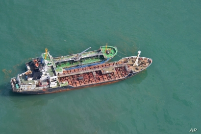 This Japan Ministry of Defense photo shows North Korean-flagged tanker SAM JONG 2, bottom, alongside MYONG RYU 1, a vessel of unknown nationality, in the East China Sea, May 24, 2018, in a suspected transferring of fuel.
