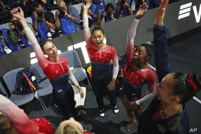 Team U.S.A. with Simone Biles, second right, celebrates winning the gold medal in the women's team final at the Gymnastics…