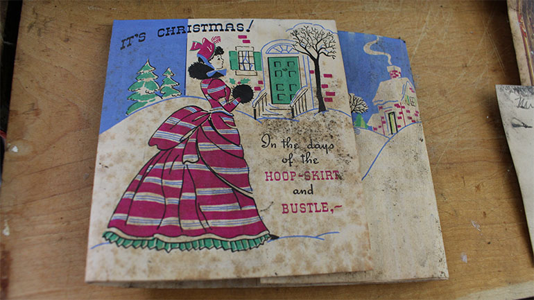 "Card front: ""It's Christmas! In the days of the hoop-skirt and bustle,"""