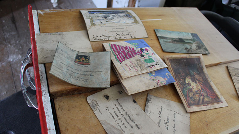 An old kitchen drawer displays a collection of cards that slipped behind the downstairs fireplace mantles over the years.