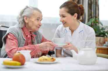 Hospice Nutrition - Elderly woman and caregiver at a table eating