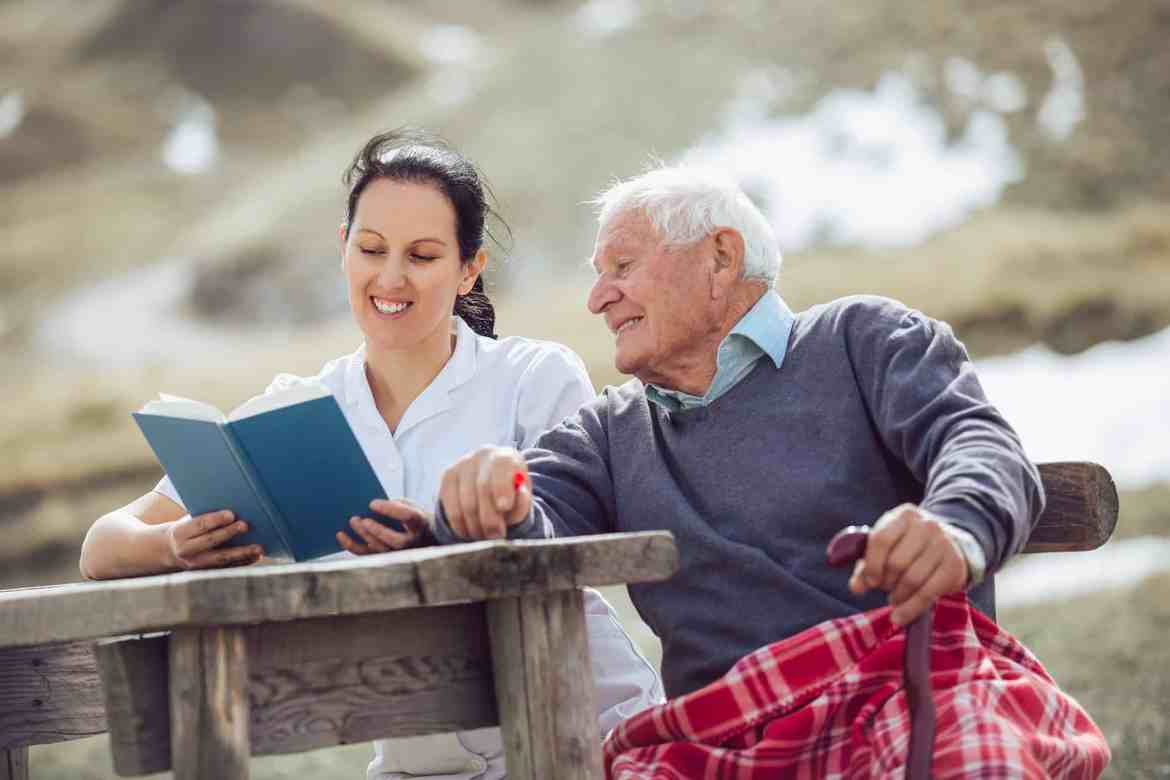 Hospice Patient and Caregiver Reading Together Outside