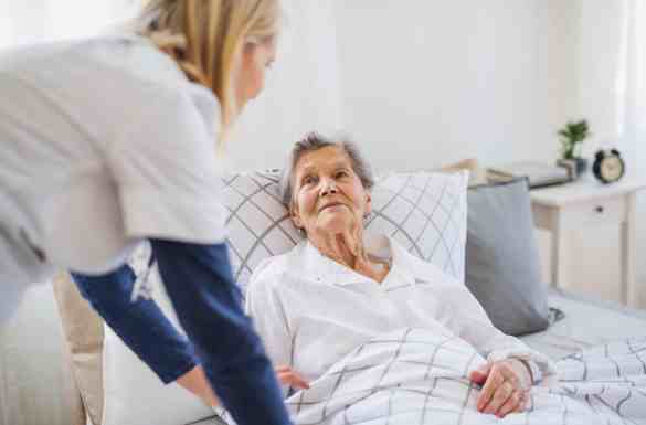 Hospice nurse assisting a hospice patient laying down