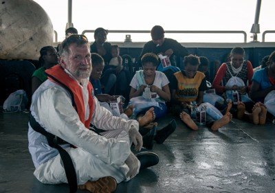 Dr Simon Bryant sits close to a group of women that have just been brought on board the Phoenix.
