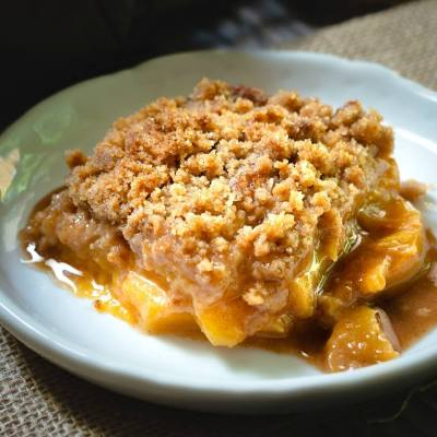 Close up of a piece of Homemade Fresh Peach Crisp and juices