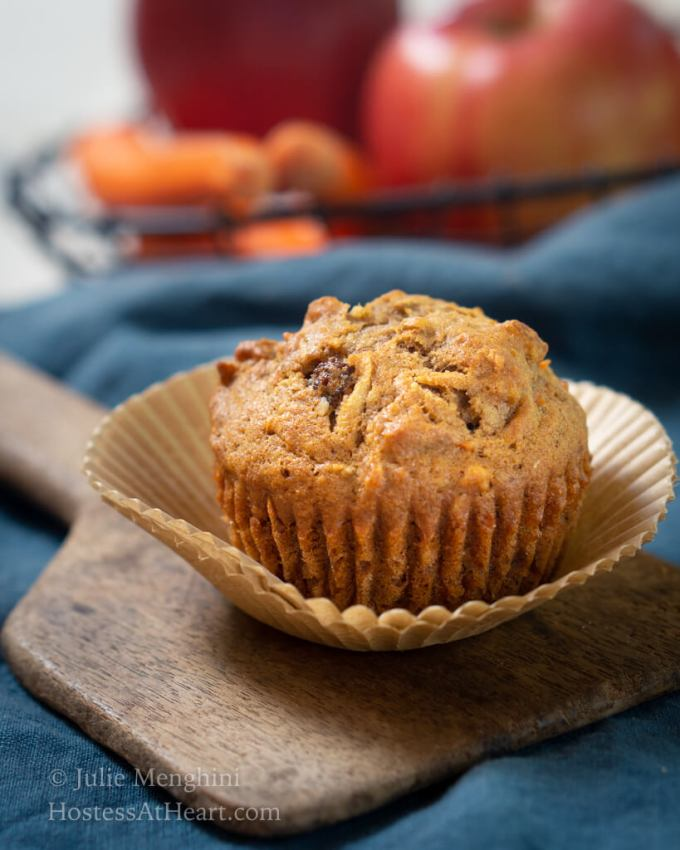 Side view of hrvest muffin with carrots and apples in the rear