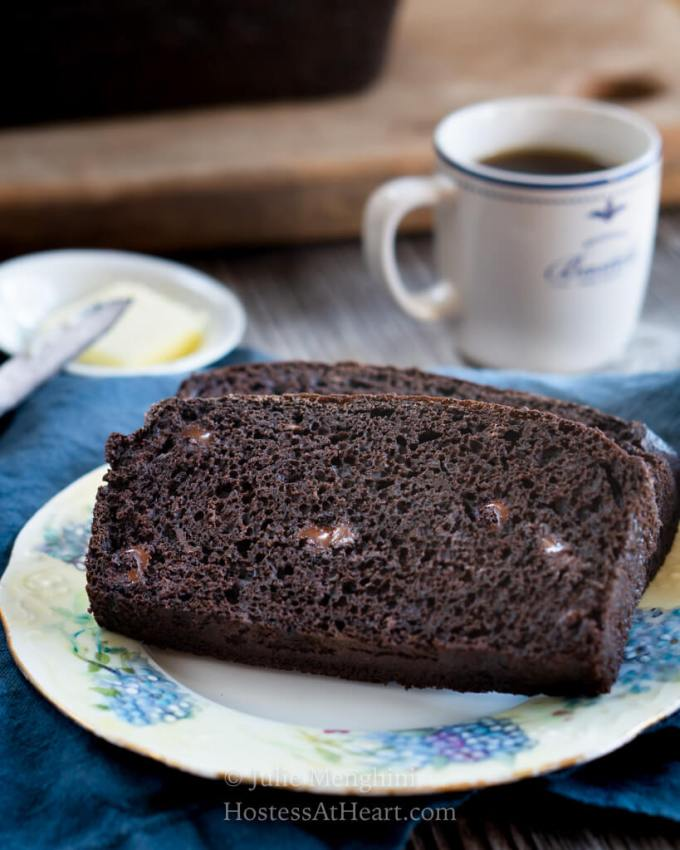 Two slices of dark chocolate banana bread on a plate with coffee