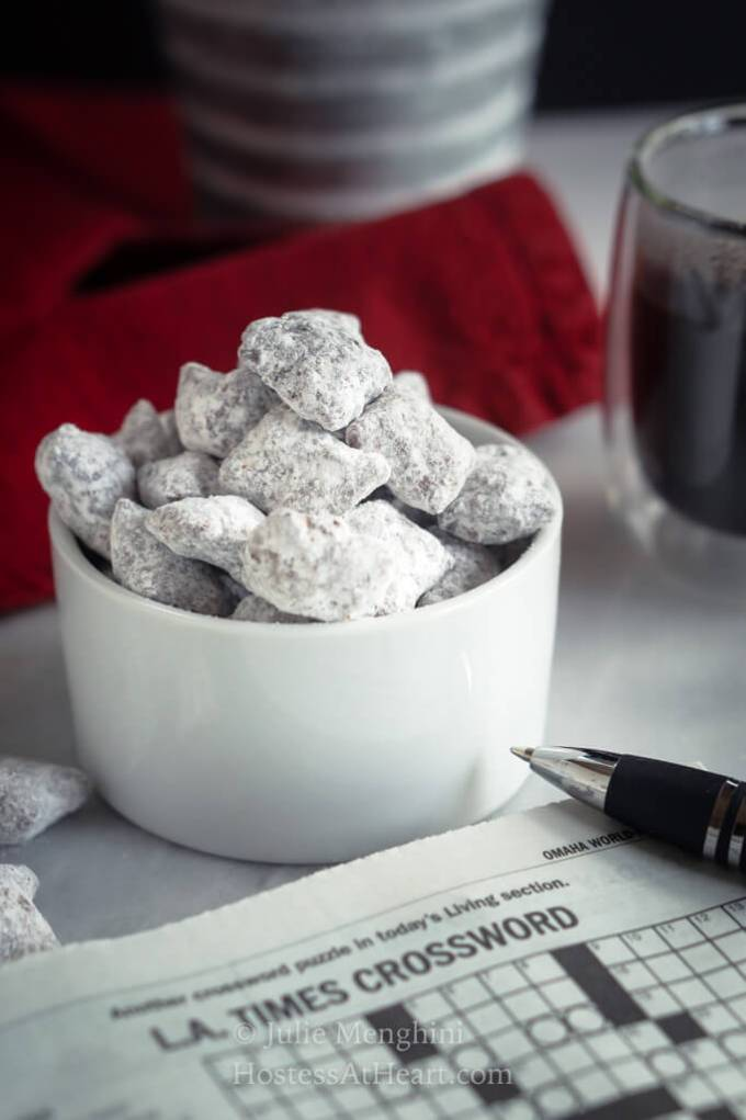 Close up shot of puppy chow with a cup of coffee and crossword puzzle