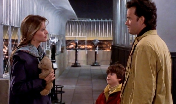 Heroine holding teddy bear and and hero with son facing her, all on top of the Empire State Building roof