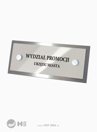 Tabliczka z oznaczeniem pomieszczenia obok drzwi. Tabliczka ze stali nierdzewnej. Przestrzenne litery, oryginalny kształt o powierzchnia tablicy wykończona na połysk.