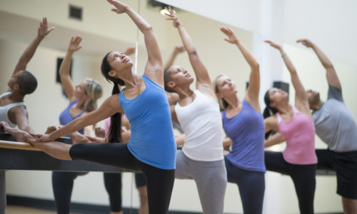 A multi-ethnic group of adults are taking a barre exercise class together at a studio.