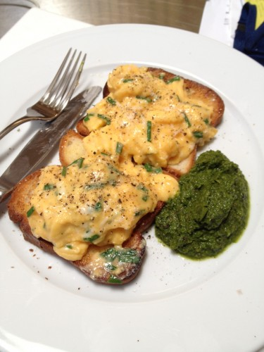 Scrambled eggs on two slices of toast with salsa verde