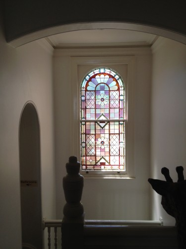 Beautiful stained-glass feature window halfway up the staircase