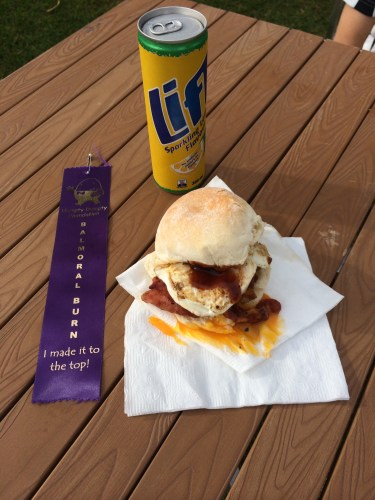 A runner's ribbon, a sugary drink and my bacon and egg roll with the yolk on the napkin rather than the roll